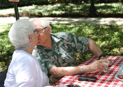 Elderly Man and Elderly Woman Kissing Outdoors