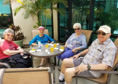 Group of Four Seniors Sitting Outside Having a Beverage