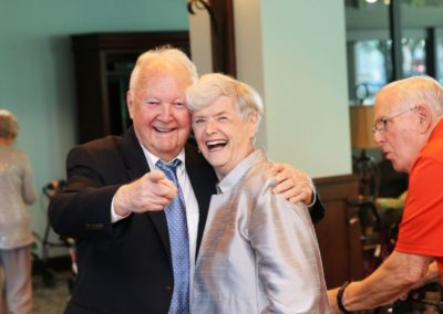 Elderly Man Pointing at the Camera With His Arm Around an Elderly Woman