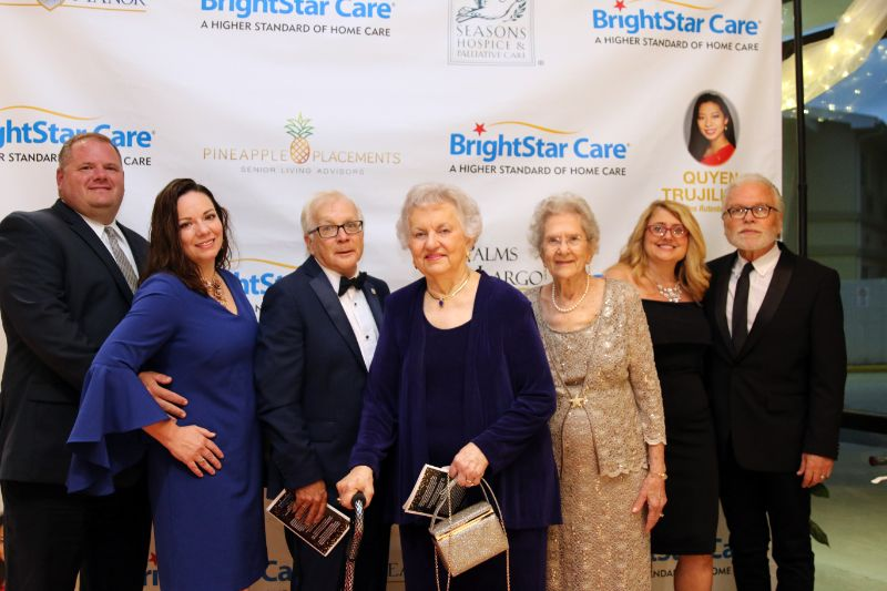 Group of Seven People Standing in front of a BrightStar Care Sign