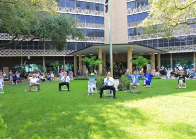 Group of People Sitting in Chairs on the Grass at Mease Life Retirement Home with Their Hands Raised