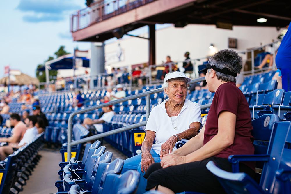 Two Seniors Attending a Baseball Game